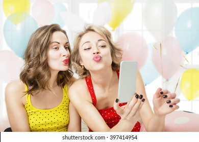 Air kiss. Selfie,  video call over the Internet. Two beautiful woman playful having fun. Pijamas party cool active mood festive atmosphere