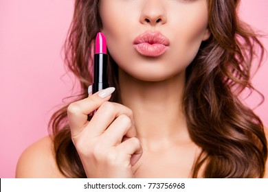 Air kiss for you. Close up cropped shot of femenine gorgeous charming adorable lady with amazing wavy hair do, tube of hard pink pomade in arm. Pampering, lips correction concept