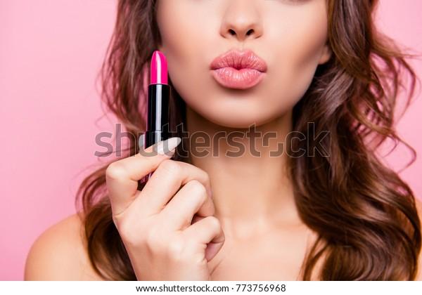 エアキスして。見事な波状の髪をした美しい女性が腕に硬いピンクのポマードのチューブを持つ、女性のクロップショットの接写。パンパリング、唇の修正のコンセプト