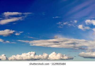 air landscape in the blue sky with long white and gray abstract clouds and beams