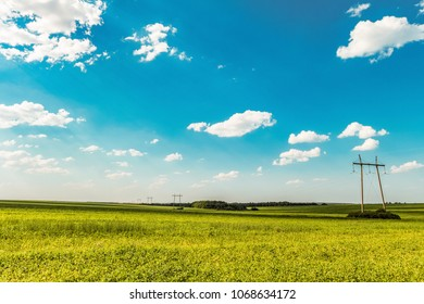 Air line supports. Steel overhead transmission line masts in a green meadow with sunny blue sky. Wide-angle.