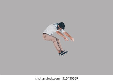 In the air. Mid-air shot of handsome young man jumping and gesturing against background