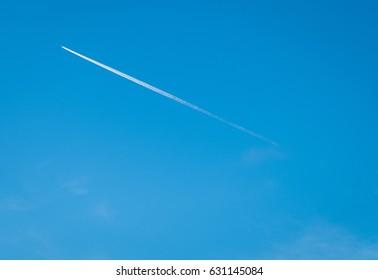 air plane jet trail in a bright sky