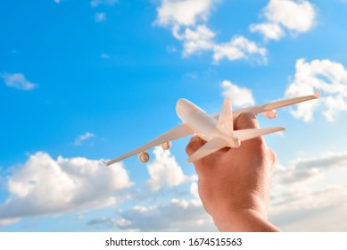 Air plane in man hand over sky scape background. Male hand holding toy airplane model over blue sky scape background with copy space, concept of vacation and travel.