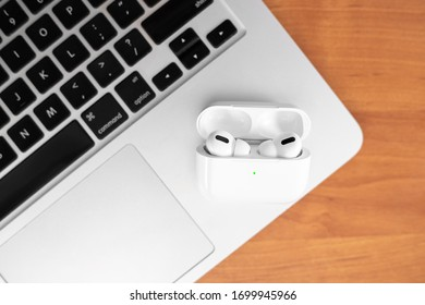 Air Pods Pro. macbook. with Wireless Charging Case. New Airpods pro on wooden background. Airpods. Copy space