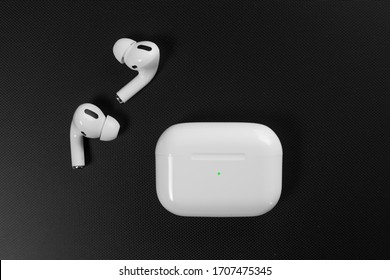 Air Pods Pro. with Wireless Charging Case. New Airpods pro on black background. Airpods Pro. Copy space. white wireless headphones on black surround background