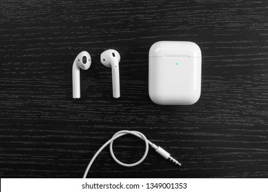 Air Pods with Wireless Charging Case. New Airpods 2019 on  black background. entangled 3.5 headphones
