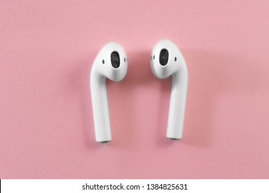 Air Pods. with Wireless Charging Case. New Airpods 2019 on pink background. Airpods. female headphones. Scissors cut the cable 3.5 headphones