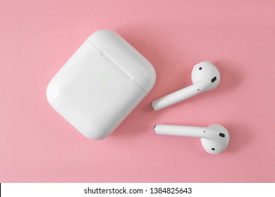 Air Pods. with Wireless Charging Case. New Airpods 2019 on pink background. Airpods. female headphones.