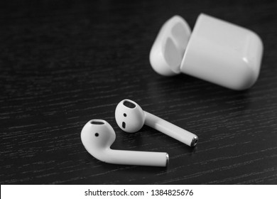 Air Pods. with Wireless Charging Case. New Airpods 2019 on black background. Airpods. Copy space