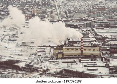 Air pollution by smoke coming out of two factory chimneys. Industrial zone in the city. aerial view. white thick smoke from tall factory pipes. top view of the heating plant.