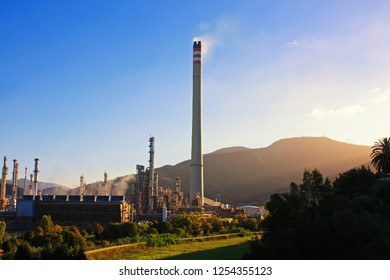 Air pollution by smoke coming out of factory chimney. Industrial zone in the city. North Spain, Cantabria, Muskiz