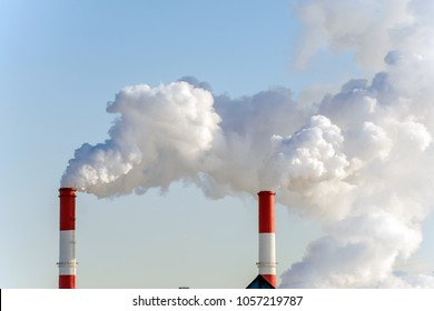 Air pollution in the city. Smoke from the chimney on blue sky background