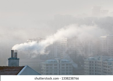 air pollution in city. smoke rising from chimney