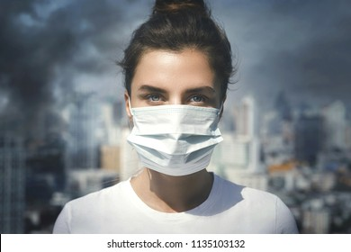 Air pollution in the city. Woman wearing face mask for protection.