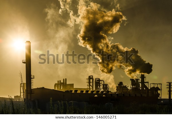 Air pollution coming from factory smoke stacks over sunset. Global concept earth preserving. Halt global warming