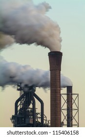 Air pollution of a factory with several chimneys in the evening