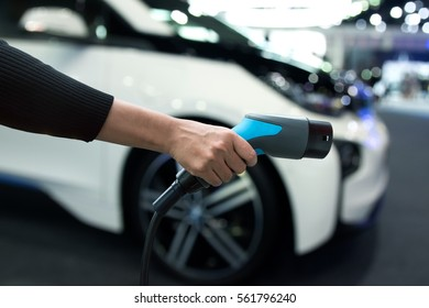 Air pollution and reduce greenhouse gas emissions concept. Hand holding and charging Electric car with blur electric car view background.