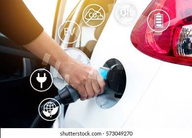Air pollution and reduce greenhouse gas emissions concept. Hand holding Electric charging vehicle car and icons with blur cars background.