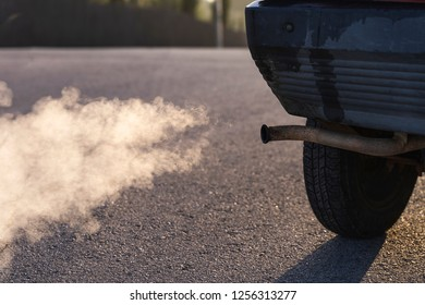 Air pollution from vehicle exhaust pipe on road. Pollution of environment by combustible gas of car.