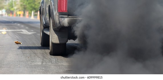 Air pollution from vehicle exhaust pipe on road.