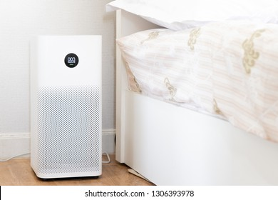 Air purifier in clear white bedroom