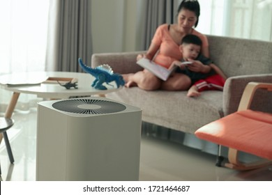 air purifier in living room with mother and kid reading inside home