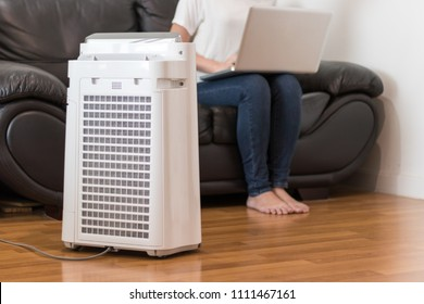Air purifier in a living room, woman working with laptop with filter for clean room
