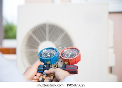 Air repair mechanic using measuring pressure gauge equipment for filling home air conditioner after cleaners and checking maintenance outdoor air compressor unit.