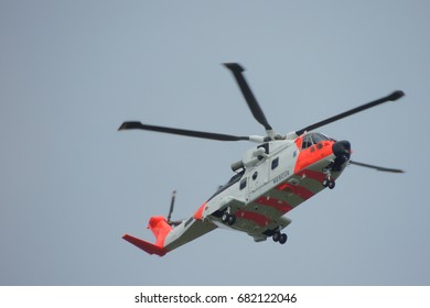 An air sea rescue helicopter above Portwrinkle harbour, on the coast path between Looe in Cornwall and Plymouth and Devon