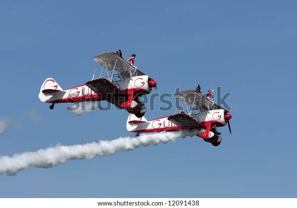 Air show. Two girls performing acrobatics on a airplane´s wing.