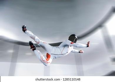 Air skydiving sports Dubai UAE.flying people in Dubai wind tunnel . indoor skydiving air. Ninja men in white suit.