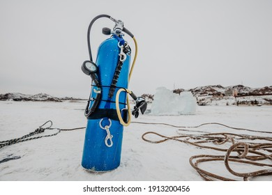 An air tank with a regulator attached standing on the ice surface of a frozen lake