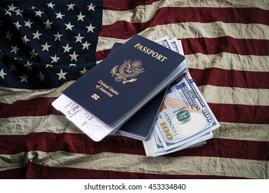 Air ticket in US passport on 100 US dollar bill with United State of America flag background, concept for travel time