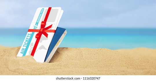 Air tickets as  gift with red ribbon and bow. Passport and air tickets in the sand on the beach of the sea. Vacation or honeymoon on the paradise islands