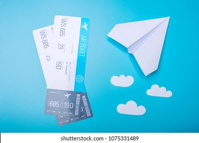 Air tickets and paper plane on blue pastel background, topview. The concept of air travel and holidays