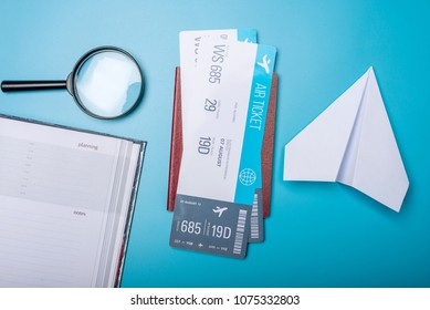 Air tickets with passport and paper plane on blue background, topview. Bright Pastel background. The concept of air travel and holidays