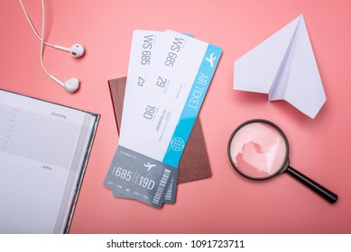 Air tickets with passport and paper plane on pink background, topview. Bright Pastel background. The concept of air travel and holidays
