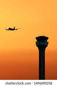 Air traffic control tower with an airplane taking off at sunset
