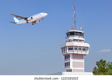 Air traffic control tower in international airport with passenger airplane jet take off on blue sky