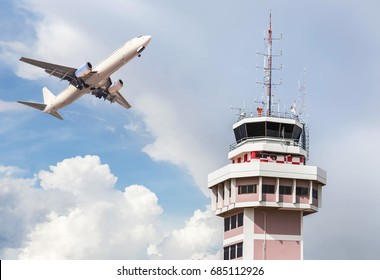 Air traffic control tower in international airport with white passenger airplane jet taking off on sky