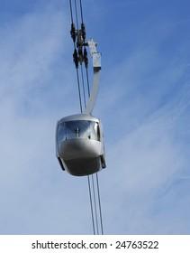 An Air Tram, Cable Car, travels through the blue sky.