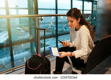 Air travel concept. Young casual woman on smart phone at gate waiting in terminal sitting with hand luggage