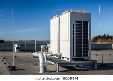 Air vents on the roof of building in functional and operational condition. Around are seen vent pipes and lightning rods. Sky is blue and the background is slightly blurred, focus on ventilation unit.