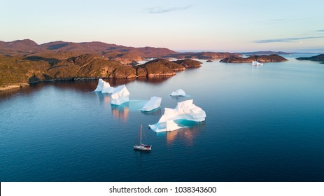 Air view to icebergs and yacht. Amazing Greenland.