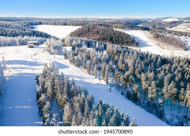 Air view on the winter sports slopes at the ski lift carousel Winterberg. Sledding slope and ski slopes between snow covered spruce forests. - Shutterstock ID 1945700890