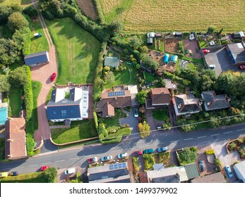 Air view of rural housing in Somerset with gardens and road