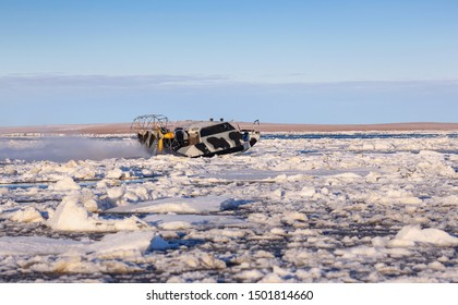Airboat (air boat) crosses river estuary  covered by ice floes. Off-road transport, passenger and cargo transportation in the off-season in the Arctic. Anadyr estuary, Chukotka, Siberia, Russia.