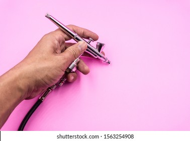 Airbrush spray work double action professional Tool in male hand for painting hobby, art, decoration, makeup Pink background.
