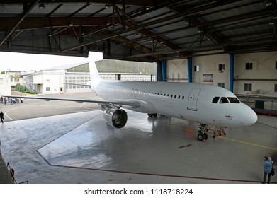 """Airbus A320 standing in the hangar and people walking around. Press-tour to the State Aircraft Repair Plant """"410"""". June 7, 2018. Kiev, Ukraine"""